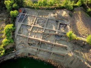 Havadan  Gusir Höyük Gusir Höyük'te kazı alanının en üst kesiminde açığa çıkarılan yapı kalıntıları yerleşim düzeni hakkında fikir verir. Burada köşeleri yuvarlatılmış, kareye yakın planlı merkezi bir yapı ve ona eklemlenmiş dikdörtgen planlı mekânlar görülmektedir. Bu görünümü ile adeta bir yoncayı andıran yapılardan merkezdekinin çapı 10 metreyi bulur. Büyüklüğü kadar, küçük mekânlardan merkezdeki yapıya geçişlerin olması bu yapının özel bir işlevi olduğunu düşündürür. Mekânın içindeki dikilitaşlar da bu görüşü destekler. Göl kenarında, teraslar halinde yapılan kazılar, Gusir Höyük'te farklı zamanlara tarihlenen birçok tabakanın olduğunu ortaya koyar. Bu tabakalar yuvarlak planlı yapılardan dörtgen planlı yapılara geçişin izlenebildiği örnekler barındırmaktadır.