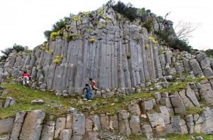 """LAV SÜTUNLARI  Kula Jeoparkı'nın görülmeye değer ilginç oluşumlarından biri de """"bazalt sütunları"""". En dikkat çekici örnekleri Kula ilçesine bağlı Çakırca köyünde bulunan bazalt sütunlarının, lav akıntısının yüksek ve dik bir uçurumdan düşerken soğuyup katılaşmasıyla oluştuğu düşünülüyor."""