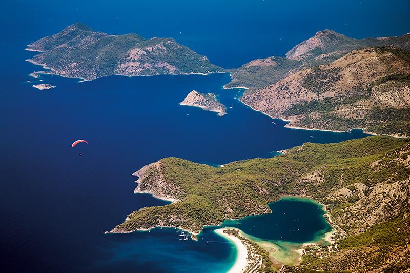 Ölüdeniz, Karacaören Koyu ve Gemiler Adası, Babadağ'dan yamaç paraşütüyle uçanların manzarasını süslüyor. Lykialılar antikçağda Ölüdeniz'e ışık ve güneş diyarı diyorlardı. Fotoğraf: Tolga Sezgin
